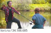 Fishing on nature - big brother gives a fishing rod to his little brother. Стоковое видео, видеограф Константин Шишкин / Фотобанк Лори