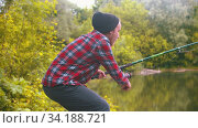 Young man sitting on fishing - pulling the rod and spinning the roulette. Стоковое видео, видеограф Константин Шишкин / Фотобанк Лори