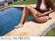Mid section of woman applying sunscreen on her legs. Стоковое фото, агентство Wavebreak Media / Фотобанк Лори