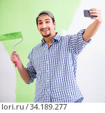 Young painter doing renovation at home. Стоковое фото, фотограф Elnur / Фотобанк Лори