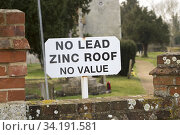 No Lead Zinc Roof No Value sign outside church to deter potential thieves who target churches for their lead roofs, Ellingham, Norfolk, England, UK. Стоковое фото, фотограф Ian Murray / age Fotostock / Фотобанк Лори