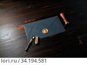 Купить «Blank black paper envelope with golden wax seal, stamp and spoon on wood table background. Mockup for your design.», фото № 34194581, снято 13 июля 2020 г. (c) easy Fotostock / Фотобанк Лори