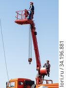Купить «Orenburg, Russia - May, 26, 2020: Worker in a basket of a telescopic aerial platform against a blue sky», фото № 34196881, снято 26 мая 2020 г. (c) Вадим Орлов / Фотобанк Лори
