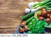 Green fresh washed wet vegetables on a table on a wooden background with copy space, healthy diet natural food and vitamin vegetarian organic food tomatoes, onions, leek cucumbers parsley. Стоковое фото, фотограф Светлана Евграфова / Фотобанк Лори