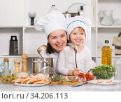 Купить «Happy girl and her mother are standing with ladle and soup together», фото № 34206113, снято 27 января 2018 г. (c) Яков Филимонов / Фотобанк Лори