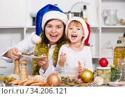 Купить «Mother and her young daughter are satisfied of dish for New Year», фото № 34206121, снято 27 января 2018 г. (c) Яков Филимонов / Фотобанк Лори