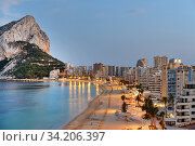 Купить «Panoramic view from above of Calpe cityscape. Street lights illuminating seafront promenade during sunset. Empty sandy beach and rocky mountain of Penon de Ifach. Costa Blanca Alicante province, Spain», фото № 34206397, снято 15 июня 2020 г. (c) Alexander Tihonovs / Фотобанк Лори