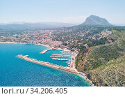 Aerial photo drone point of view coastal town of Javea with green mountains, turquoise bay Mediterranean Sea moored vessels in harbour, comarca of Marina Alta in province of Alicante, Valencia, Spain. Стоковое фото, фотограф Alexander Tihonovs / Фотобанк Лори