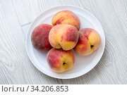 A few ripe peaches lie on a plate. Стоковое фото, фотограф Володина Ольга / Фотобанк Лори