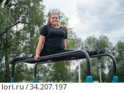 A beautiful smiling overweight young woman stretches for split on uneven bars outdoors. Fat girl gymnast doing fitness on the sports field. Sport outside on a warm summer day. Редакционное фото, фотограф Михаил Решетников / Фотобанк Лори