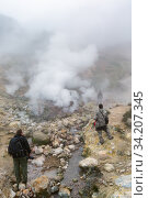 Купить «Group of tourists and photographer walking through volcanic landscape: eruption fumarole, hot springs, gas-steam activity in crater active volcano», фото № 34207345, снято 7 сентября 2014 г. (c) А. А. Пирагис / Фотобанк Лори