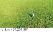 Low orbital flight around man on green grass with notebook pad at yellow rural field. Стоковое видео, видеограф Александр Маркин / Фотобанк Лори