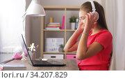 Купить «girl in headphones with laptop computer at home», видеоролик № 34207829, снято 14 июня 2020 г. (c) Syda Productions / Фотобанк Лори