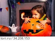 Curious Halloween girl with huge pumpkin at home. Стоковое фото, фотограф Сергей Новиков / Фотобанк Лори