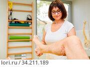 Physiotherapeutin behandelt Knieschmerzen mit Osteopathie in der Naturheilkunde. Стоковое фото, фотограф Zoonar.com/Robert Kneschke / age Fotostock / Фотобанк Лори
