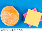 Front view hamburger roll bun colored sticky note pads wooden background. Стоковое фото, фотограф Zoonar.com/Artur Szczybylo / easy Fotostock / Фотобанк Лори