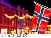 Norwegian flag hanging from a pole in Tromso city centre in Christmas period after dusk, Norway. Стоковое фото, фотограф Zoonar.com/Pawel Opaska / easy Fotostock / Фотобанк Лори