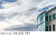 Купить «Clear Panorama Exterior of a modern building with shiny and reflective glass windows. The blue sky filled with clouds in the background is mirrored on the glass windows.», фото № 34226781, снято 4 августа 2020 г. (c) easy Fotostock / Фотобанк Лори
