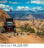 Купить «Off road vehicle and La Sal Mountain view in Moab. Parked off road vehicle overlooking dramatic cliffs and the magnificent La Sal Mountain in Moab, Utah. The sun shines brightly on the rugged terrain.», фото № 34228081, снято 6 августа 2020 г. (c) easy Fotostock / Фотобанк Лори