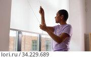 Купить «african woman closes window blinds at home», видеоролик № 34229689, снято 14 июня 2020 г. (c) Syda Productions / Фотобанк Лори