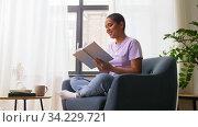 happy african american woman reading book at home. Стоковое видео, видеограф Syda Productions / Фотобанк Лори
