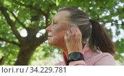 Купить «Senior woman using wireless earphones in the park», видеоролик № 34229781, снято 14 октября 2019 г. (c) Wavebreak Media / Фотобанк Лори