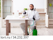 Young male contractor doing pest control at home. Стоковое фото, фотограф Elnur / Фотобанк Лори
