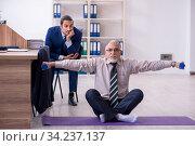 Купить «Two employees doing physical exercises at workplace», фото № 34237137, снято 7 октября 2019 г. (c) Elnur / Фотобанк Лори