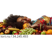 African American Black woman smiles at the camera while lying among fruits. Стоковое фото, фотограф Алексей Кузнецов / Фотобанк Лори