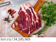 Купить «Preparation of raw beef fillet with parsley and garlic on wooden board», фото № 34245969, снято 3 августа 2020 г. (c) Яков Филимонов / Фотобанк Лори