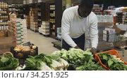 African American man shopping in organic food store, choosing fresh salad. Стоковое видео, видеограф Яков Филимонов / Фотобанк Лори