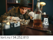 Detective with tweezers finds evidence, crime scene. Стоковое фото, фотограф Tryapitsyn Sergiy / Фотобанк Лори