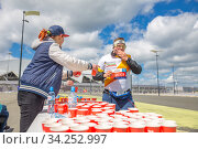 Russia, Samara, June 2019: volunteers give out glasses of water to athletes running a marathon during a city holiday. Редакционное фото, фотограф Акиньшин Владимир / Фотобанк Лори