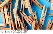 close up of wooden clothespins on blue background. Стоковое видео, видеограф Syda Productions / Фотобанк Лори