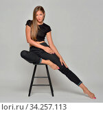 Portrait of the sexy beautiful woman in black posing in studio with grey background. She is sitting on the high chair. Стоковое фото, фотограф Zoonar.com/© Dmitry Raikin / easy Fotostock / Фотобанк Лори