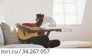 Купить «Man playing guitar at home», видеоролик № 34267057, снято 13 декабря 2018 г. (c) Wavebreak Media / Фотобанк Лори