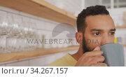 Купить «Handsome man drinking coffee indoors», видеоролик № 34267157, снято 13 декабря 2018 г. (c) Wavebreak Media / Фотобанк Лори