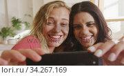 Two young woman friends taking a selfie indoors. Стоковое видео, агентство Wavebreak Media / Фотобанк Лори