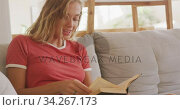 Beautiful woman reading books while sitting on the couch. Стоковое видео, агентство Wavebreak Media / Фотобанк Лори