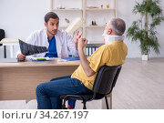 Old neck injured man visiting young male doctor radiologist. Стоковое фото, фотограф Elnur / Фотобанк Лори