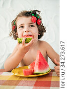 Hungry cute girl devours watermelon slices, refreshing summer dessert. Has strawberry hair clips acting being goofy funny. Стоковое фото, фотограф José Carlos Carrillo Cabrera / easy Fotostock / Фотобанк Лори