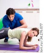 Купить «Fitness instructor helping sportsman during exercise», фото № 34276077, снято 10 июля 2018 г. (c) Elnur / Фотобанк Лори