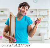 Young funny artist working on new painting in his studio. Стоковое фото, фотограф Elnur / Фотобанк Лори