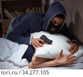 Burglar breaking into house at night to bedroom with sleeping wo. Стоковое фото, фотограф Elnur / Фотобанк Лори