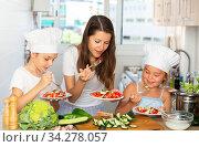 Купить «Little cooks learn with their mom how to cook a salad in the kitchen», фото № 34278057, снято 5 августа 2020 г. (c) Яков Филимонов / Фотобанк Лори