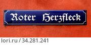 Dunkelblaues Strassenschild mit weisser Schrift an roter Hauswand: ROTER HERZFLECK ? ein historisches Gasthaus bzw. Bordell in Regensburg. Die Damen trugen... Стоковое фото, фотограф Zoonar.com/Bernhard Kuh / easy Fotostock / Фотобанк Лори
