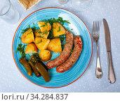 Appetizing sausages with potatoes and pickled cucumbers closeup. Стоковое фото, фотограф Яков Филимонов / Фотобанк Лори