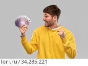 Купить «happy young man with money celebrating success», фото № 34285221, снято 22 февраля 2020 г. (c) Syda Productions / Фотобанк Лори