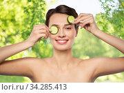 Купить «beautiful woman making eye mask of cucumbers», фото № 34285413, снято 30 ноября 2019 г. (c) Syda Productions / Фотобанк Лори