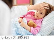 doctor measuring sick girl's temperature at home. Стоковое фото, фотограф Syda Productions / Фотобанк Лори